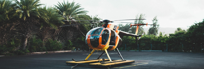Orangener Helicopter mit Palmen im Hintergrund